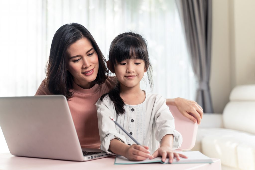 Homeschool Asian young little girl learning internet online class and do homework by using computer with mother help, teach and encourage. Daughter smile and happy to study at home together with mom.