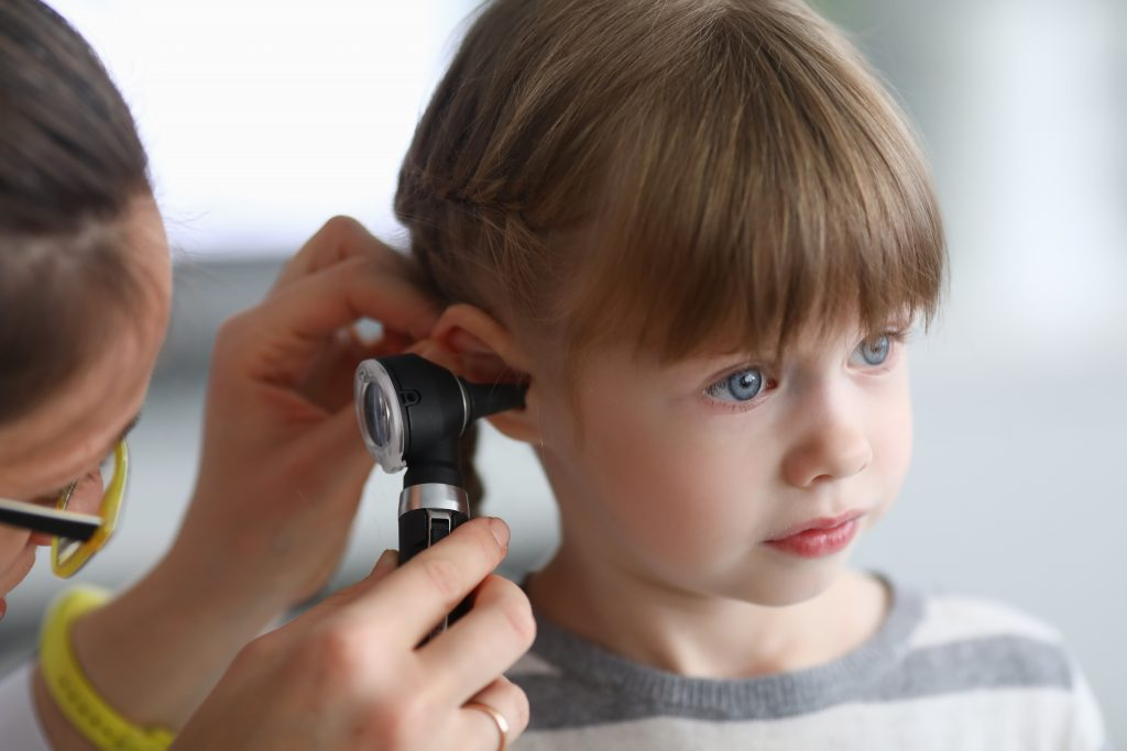 Otorhinolaryngologist examines little girl's ear with otoscope in clinic